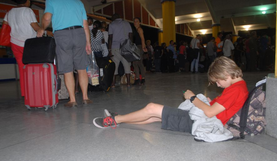 A child rests as passengers go through security screening at Moi International Airport Mombasa Kenya, Sunday, Dec. 20, 2015 after their earlier flight was involved in a bomb scare and they were evacuated to different hotels in Mombasa. (AP Photo)