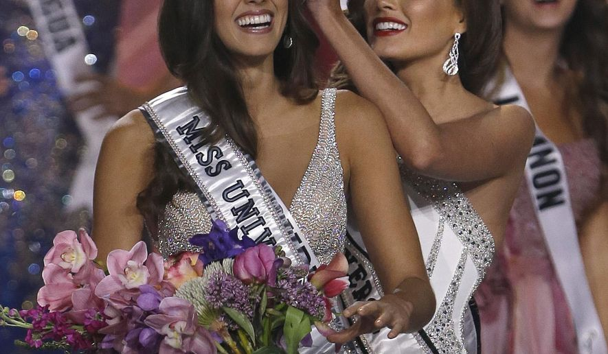FILE - In this Jan. 25, 2015, file photo, reigning Miss Universe Gabriela Isler, right, crowns the new Miss Universe, Paulina Vega of Colombia, left, during the Miss Universe pageant in Miami. Donald Trump's pageant days are over after his controversial comments about immigrants created a backlash, but the Miss Universe pageant will go on, crowning a new winner on Sunday, Dec. 20, 2015, in Las Vegas. (AP Photo/Wilfredo Lee, File)