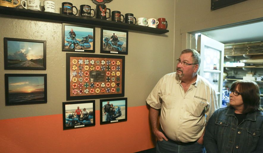 In this photo taken on Monday, Nov. 30, 2015, Norman and Janet Epperly look over photographs and memorabilia from their travels in their home in Riner, Va. During the past five years, the couple have experienced each of the 48 continental states while putting more than 90,000 miles on their Harley-Davidson Road Glide Ultra bike. (Matt Gentry /The Roanoke Times via AP) LOCAL TELEVISION OUT; SALEM TIMES REGISTER OUT; FINCASTLE HERALD OUT;  CHRISTIANBURG NEWS MESSENGER OUT; RADFORD NEWS JOURNAL OUT; ROANOKE STAR SENTINEL OUT; MANDATORY CREDIT