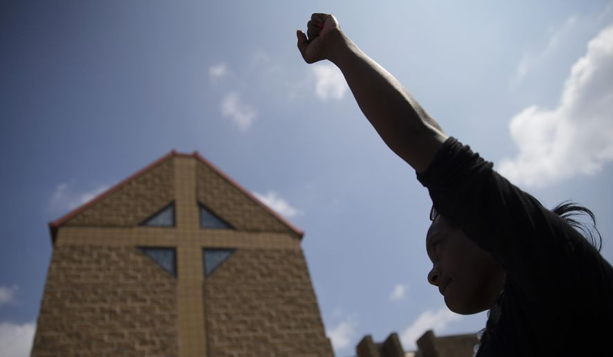 FILE - In this Tuesday, July 28, 2015 file photo, mourner JeRee Wilson holds her fist in the air outside funeral services for Samuel Dubose at the Church of the Living God in the Avondale neighborhood of Cincinnati. Dubose was fatally shot by a University of Cincinnati police officer who stopped him for a missing license plate. Volatile, racially sensitive questions of whether to charge police officers for fatal on-duty shootings, and whether jurors will convict an officer in such a case, hang over two of Ohio's largest cities. (AP Photo/John Minchillo, File)