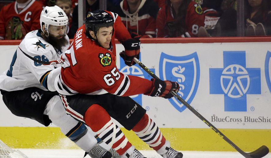 Chicago Blackhawks right wing Andrew Shaw, right, controls the puck against San Jose Sharks defenseman Brent Burns during the second period of an NHL hockey game, Sunday, Dec. 20, 2015, in Chicago. (AP Photo/Nam Y. Huh)