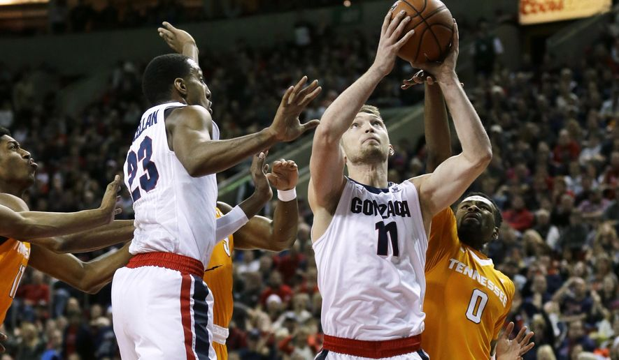 Gonzaga forward Domantas Sabonis (11) shoots next to Tennessee guard Kevin Punter (0) as Gonzaga guard Eric McClellan (23) watches during the first half of an NCAA college basketball game, Saturday, Dec. 19, 2015, in Seattle. (AP Photo/Ted S. Warren)