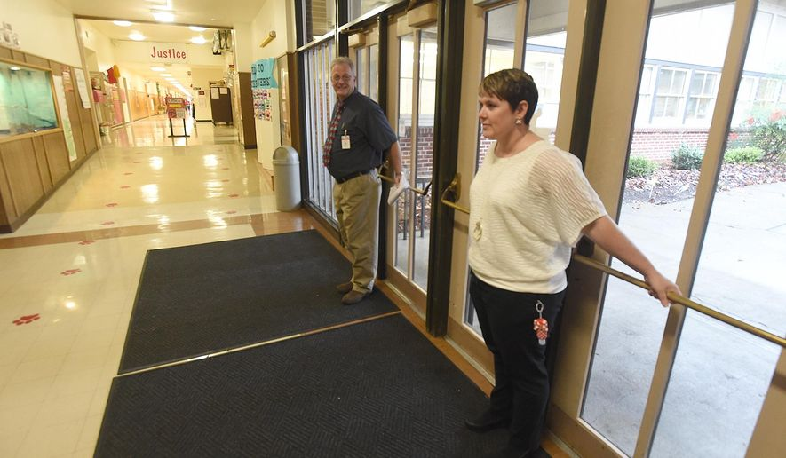 In this Dec. 9, 2015, photo, Sunrise Elementary School Principal Jodi Smith and substitute teacher Harvey Miller hold the front doors shut while nearby employees work with a troubled student who was trying to leave the building in Albany, Ore. (Mark Ylen/Albany Democrat-Herald via AP) MANDATORY CREDIT