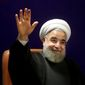 Iran's President Hassan Rouhani, who is also a member of the Experts Assembly, waves to media with an ink-stained finger, after registering his candidacy for the Feb. 26 elections of the assembly at interior ministry in Tehran, Iran, Monday, Dec. 21, 2015. (AP Photo/Ebrahim Noroozi)
