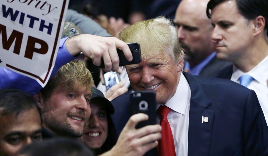 Republican presidential candidate Donald Trump poses with supporters after a campaign rally, Monday, Dec. 21, 2015, in Grand Rapids, Mich. (AP Photo/Carlos Osorio)
