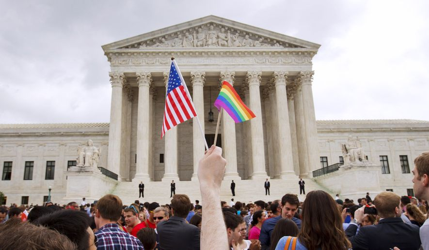 A man holds a U.S. and a rainbow flag outside the Supreme Court in Washington on June 16, 2015, after the court legalized gay marriage nationwide. (Associated Press) ** FILE **