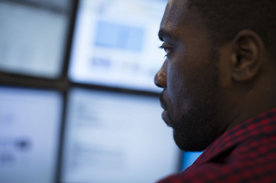 In this Wednesday, May 20, 2015 photo, Eric Dinkins, cyber security analyst associate, works at a computer station in the Cyber Security Operations Center at AEP headquarters in Columbus, Ohio. (AP Photo/John Minchillo)
