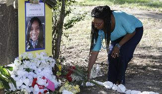 Jeanette Williams places a bouquet of roses at a memorial for Sandra Bland near Prairie View A&M University, Tuesday, July 21, 2015, in Prairie View, Texas. (Associated Press)