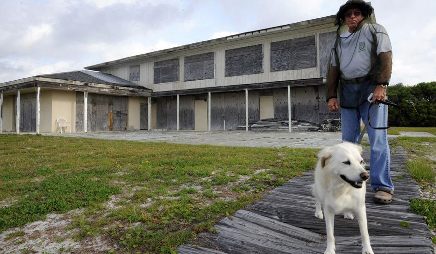 FILE - In this Friday, May 15, 2015 file photo, Ralph Gilges walks his dog Dixie outside Alabama's abandoned beachfront governor's mansion in Gulf Shores, Ala. Work began earlier this month to fix the 7,500-square-foot gubernatorial mansion that wasn't repaired after Hurricane Danny in 1997. A spokeswoman for Gov. Robert Bentley says BP grant money left over from the 2010 oil spill will cover the $1.8 million in renovations. (AP Photo/Jay Reeves, File)