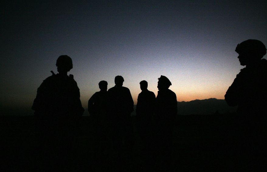 FILE - In this Sunday, Oct. 18, 2009 file photo, U.S. Army soldiers stand with Afghan policemen before a joint patrol of Qalanderkhail, outside of Bagram Air Field in Afghanistan. An Afghan official says that a suicide bomber has killed three foreign troops in an attack on a joint Afghan-NATO foot patrol on Monday, Dec. 21, 2015. Mohammad Asim Asim, governor of Parwan province said an attacker on a motorcycle rammed a group of eight troops as they patrolled a village near Bagram Airfield, 45 kilometers (28 miles) north of Kabul. (AP Photo/Maya Alleruzzo, File)