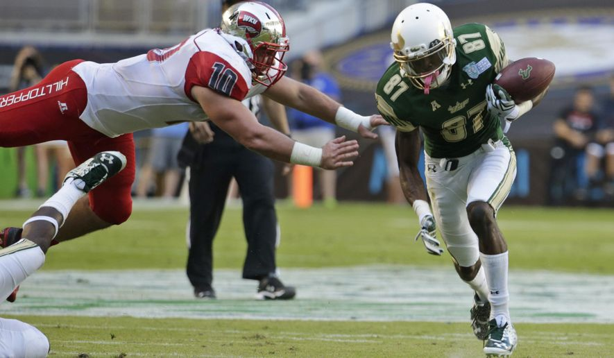 South Florida wide receiver Rodney Adams (87) runs on his way to scoring a touchdown as Western Kentucky linebacker Nick Holt (10) misses a tackle during the first half of the NCAA college football Miami Beach Bowl game, Monday, Dec. 21, 2015, in Miami. (AP Photo/Lynne Sladky)