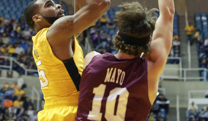 West Virginia guard Jaysean Paige (5) shoots over Eastern Kentucky forward Nick Mayo (10) during the first half of an NCAA college basketball game Monday, Dec, 21, 2015, in Morgantown, W.Va. (AP Photo/Raymond Thompson)