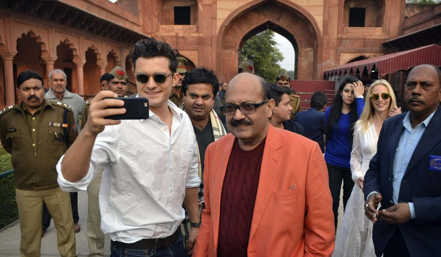 In this Sunday, Dec. 20, 2015, photo, British actor Orlando Bloom, front left, takes a selfie as Indian lawmaker Amar Singh, front right, watches on arrival at the Taj Mahal in Agra, India. Indian officials say Bloom has arrived in New Delhi after being turned away a day earlier because he did not have a valid visa. (AP Photo/ Pawan Sharma)