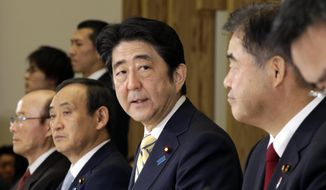 Japan's Prime Minister Shinzo Abe, second right, speaks during a meeting of Cabinet ministers on a new national stadium construction plan for the 2020 Tokyo Olympics at Abe's official residence in Tokyo Tuesday, Dec. 22, 2015. At right is Toshiaki Endo, minister in charge of the 2020 Tokyo Olympics.  Japan has selected a new design for the main stadium for the 2020 Tokyo Olympics after scrapping an earlier plan as too costly. Prime Minister Abe announced Tuesday that the winner is a design by renowned Japanese architect Kengo Kuma, construction company Taisei Corp. and Azusa design office.(AP Photo/Eugene Hoshiko, Pool)