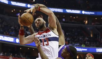 Washington Wizards center Marcin Gortat (13) fights for control of the ball with Sacramento Kings forward DeMarcus Cousins, rear, and guard Rajon Rondo during the first half of an NBA basketball game Monday, Dec. 21, 2015, in Washington. Wizards forward Jared Dudley is at right. (AP Photo/Carolyn Kaster)