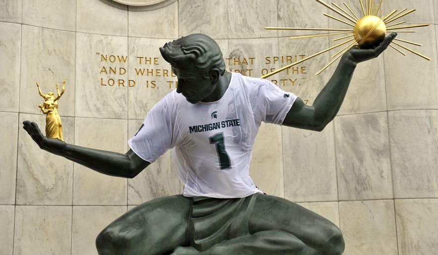The Spirit of Detroit statue appears with a Michigan State football jersey in downtown Detroit on Monday, Dec. 21, 2015, in honor of the Spartans' playoff game against Alabama in the Cotton Bowl on Dec. 31. (John T. Greilick/The Detroit News via AP)