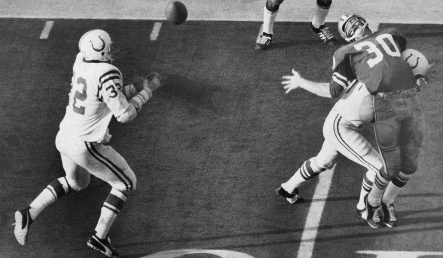 FILE - In this Jan. 17, 1971, file photo, Baltimore Colts linebacker Mike Curtis reaches for the ball to make an interception of a Dallas Cowboys pass intended for Dan Reeves (30) in the fourth period of  Super Bowl V in Miami, Fla. The first Super Bowl under the merger ended in high drama, but only after both teams struggled through 60 minutes of turnovers. (AP Photo, File)