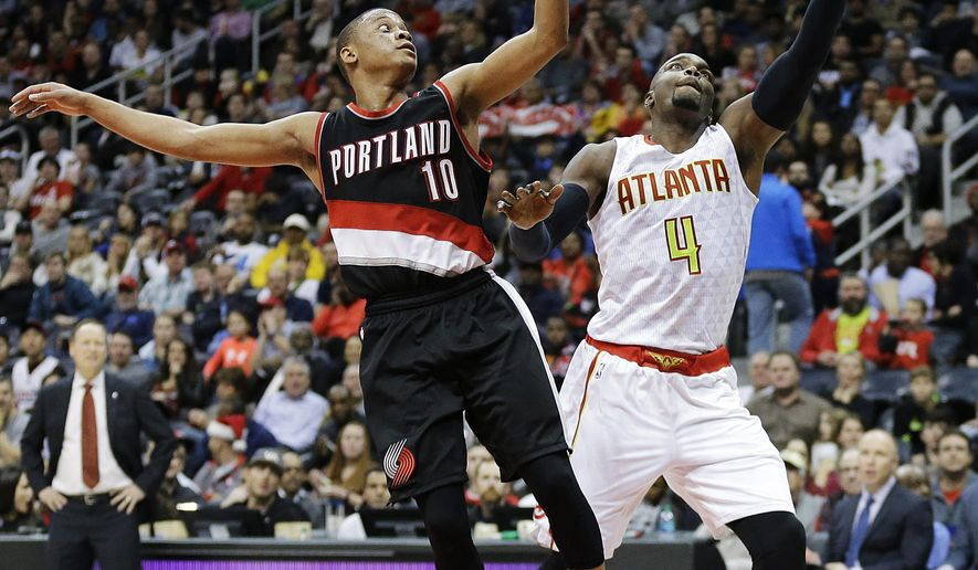 Atlanta Hawks' Paul Millsap, right, saves a pass from going out of bounds in front of Portland Trail Blazers' Tim Frazier in the second quarter of an NBA basketball game Monday, Dec. 21, 2015, in Atlanta. (AP Photo/David Goldman)