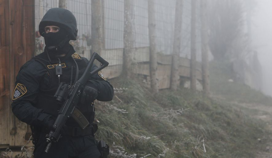 """A Bosnian police officer secures an area in a Sarajevo suburb as authorities look for 15 people suspected of being in """"close contact"""" with the Islamic State. (Associated Press)"""