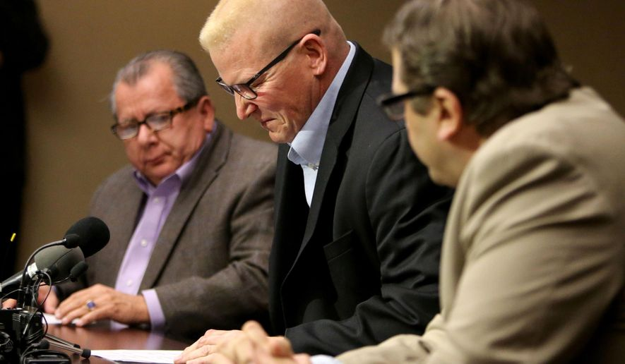 St. Paul Central High teacher John Ekblad, middle, prepares to speak to the media next to his attorneys Philip Villaume, left, and Jeffrey Schiek, Tuesday, Dec. 22, 2015, in Bloomington, Minn. Ekblad says he suffered a traumatic brain injury Dec. 4 while trying to break up a fight. A 16-year-old student pleaded guilty Friday to felony assault against Ekblad. (David Joles/Star Tribune via AP)  MANDATORY CREDIT; ST. PAUL PIONEER PRESS OUT; MAGS OUT; TWIN CITIES LOCAL TELEVISION OUT