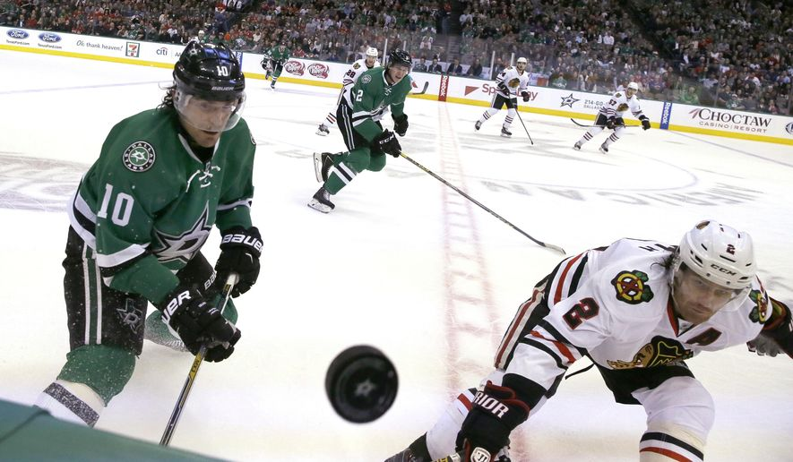 Chicago Blackhawks defenseman Duncan Keith (2) and Dallas Stars left wing Patrick Sharp (10) chase the puck during the first period of an NHL hockey game Tuesday, Dec. 22, 2015, in Dallas. (AP Photo/LM Otero)