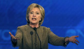 In this Dec. 19, 2015, photo. Hillary Clinton speaks during a Democratic presidential primary debate at Saint Anselm College in Manchester, N.H. Using a savvy social media campaign, in-person pleas and pithy T-shirts, three Iowa high school students have successfully lobbied Clinton to visit their small town. Clinton will appear Dec. 22 in Keota, a town of about a thousand people in southeast Iowa. (AP Photo/Jim Cole)