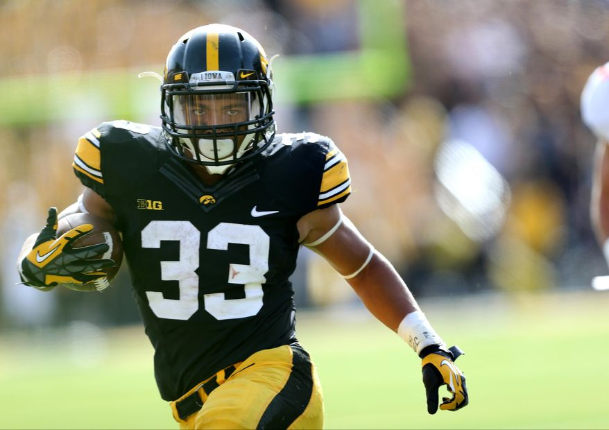 FILE - In this Oct. 10, 2015, file photo, Iowa running back Jordan Canzeri runs away an Illinois defender during the second half of an NCAA college football game in Iowa City, Iowa. Iowa reached its first Rose Bowl in 25 years despite a series of injuries. An extended rest should help players like Canzeri get ready for the Hawkeyes biggest game in years.  (AP Photo/Justin Hayworth, File)
