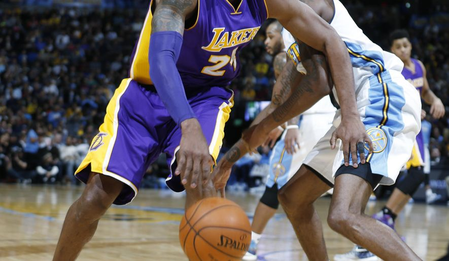 Los Angeles Lakers forward Kobe Bryant. left, drives past Denver Nuggets forward Will Barton in the first half of an NBA basketball game, Tuesday, Dec. 22, 2015, in Denver. (AP Photo/David Zalubowski)