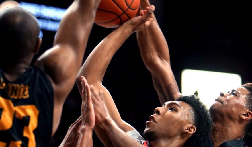 Arizona guard Allonzo Trier (11) drives into the lane between Long Beach State forward Roschon Prince, left, guard A.J. Spencer (15) and guard Nick Faust (2) during the first half of an NCAA college basketball game Tuesday, Dec. 22, 2015, in Tucson, Aria. (Kelly Presnell/Arizona Daily Star via AP)