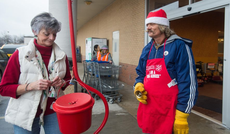 In this photo taken on Monday, Dec. 21, 2015, Deb Dingman drops money into a red kettle as David Pringle ring his bell for the Salvation Army Red Kettle Drive in front of a Kroger supermarket, in Hampton Township, Mich. (Yfat Yossifor/The Bay City Times via AP) LOCAL TELEVISION OUT; LOCAL INTERNET OUT; MANDATORY CREDIT