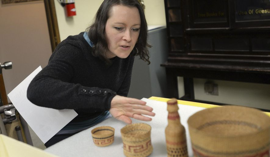 ADVANCE FOR WEEKEND DEC. 26-27, 2015 AND THEREAFTER  In this Dec. 17, 2015 photo, Ketchikan Museums director Lacey Simpson talks about painting on a small spruce root basket weaved by Selina Peratrovich in the Tongass Historical Museum storage room in Ketchikan, Alaska. When Peter Corey, former curator of the Alaska State Museum and the Sheldon Jackson Museum, died Sept. 20 in Sitka, he left behind a massive collection of Alaska Native art. Now, some of the pieces have found their way home to Ketchikan. (Taylor Balkom/Ketchikan Daily News via AP)