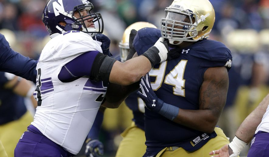 FILE - In this Nov. 15, 2014, file photo, Notre Dame's Jarron Jones (94) rushes against Northwestern offensive lineman Geoff Mogus (53) during the first half of an NCAA college football game in South Bend, Ind. Jones, who hasn't played in a game since the 11th game last season, believes he's ready to contribute again when the eighth-ranked Fighting Irish face No. 7 Ohio State in the Fiesta Bowl. He's just not sure how much. (AP Photo/Nam Y. Huh, File)