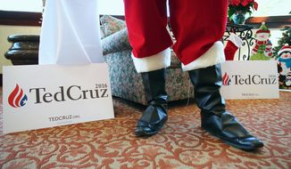 A person dressed as Santa greets guests during a Christmas-themed campaign stop for Republican presidential candidate Sen. Ted Cruz, whose campaign is offering a signature Christmas sweater for $65. (Associated Press)