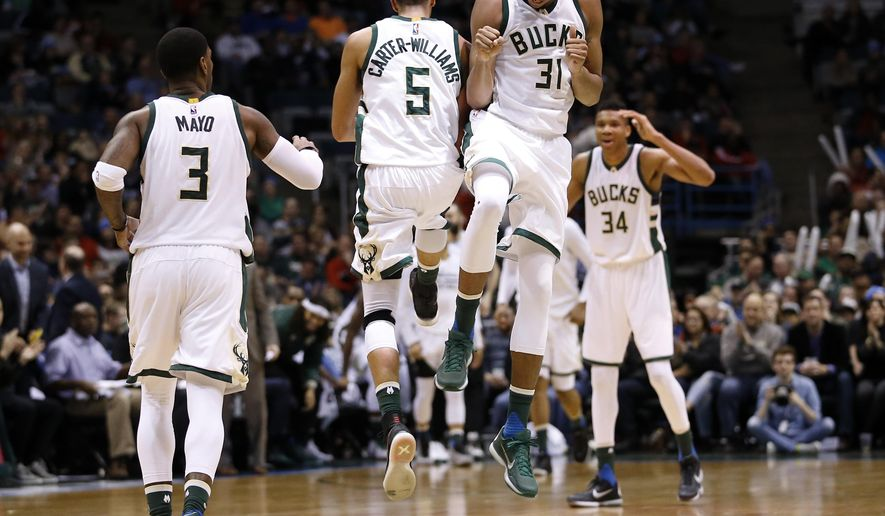 Milwaukee Bucks' John Henson (31) and Michael Carter-Williams celebrate during a break in the second half of an NBA basketball game against the Philadelphia 76ers Wednesday, Dec. 23, 2015, in Milwaukee. (AP Photo/Morry Gash)