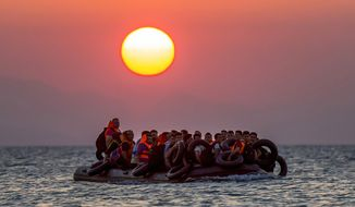 Migrants on a dinghy arrives at the southeastern island of Kos, Greece, after crossing from Turkey, Thursday, Aug. 13, 2015. Greece has become the main gateway to Europe for tens of thousands of refugees and economic migrants, mainly Syrians fleeing war, as fighting in Libya has made the alternative route from north Africa to Italy increasingly dangerous. (AP Photo/Alexander Zemlianichenko, File)