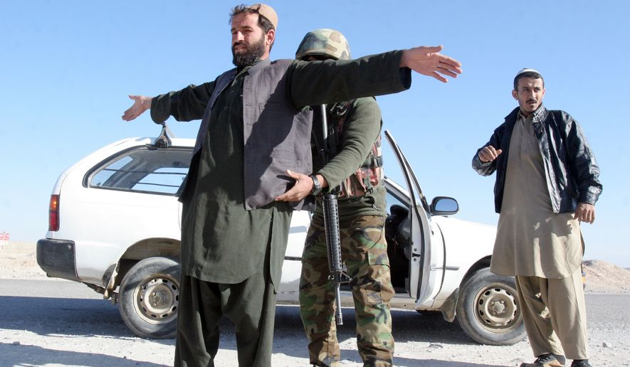 An Afghan National Army soldier searches a passenger at a checkpoint on the way to the Sangin district of Helmand province, Afghanistan, Wednesday, Dec. 23, 2015. Reinforcements have been rushed to a besieged southern district threatened for days with takeover by Taliban fighters, Afghanistan's acting defense minister said on Wednesday. (AP Photos/Abdul Khaliq)