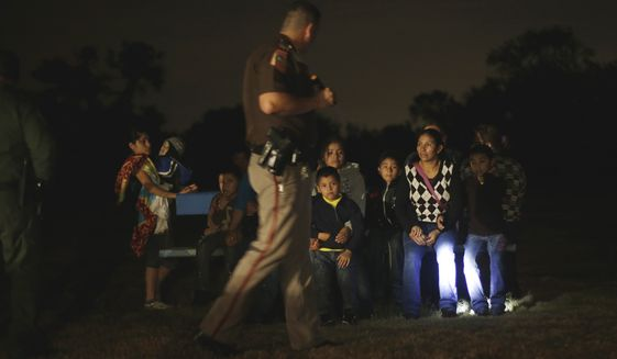 A group of immigrants from Honduras and El Salvador who crossed the U.S.-Mexico border illegally are stopped on June 25, 2014, in Granjeno, Texas. (Associated Press) **FILE**