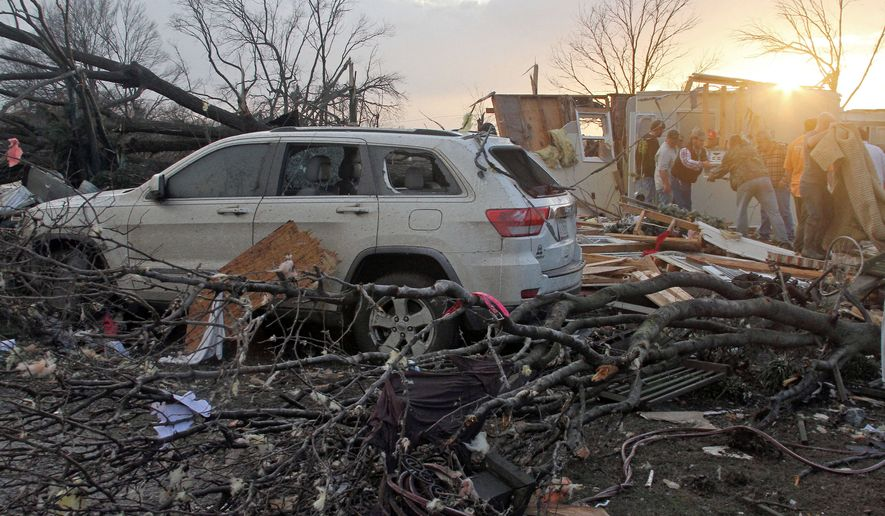 "Neighbors help salvage items from a storm-damaged home in the Roundaway community near Clarksdale, Miss., on Wednesday. A storm system forecasters called ""particularly dangerous"" killed multiple people as it swept across the country Wednesday. (The Press Register via Associated Press)"