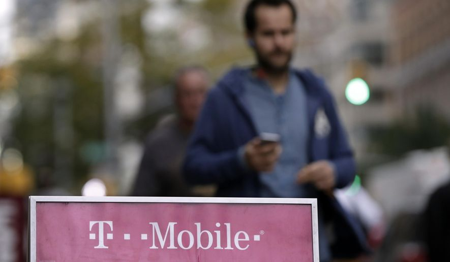 """FILE - This Oct. 14, 2015, file photo, shows people passing a T-Mobile store, in New York. T-Mobile last month switched its customers on bigger data plans to what it's calling """"Binge On,"""" which lets them watch video without using up their data. The service has caused consternation among advocates of net neutrality, the concept that Internet service providers shouldn't discriminate in favor or some content versus other content. (AP Photo/Richard Drew, File)"""