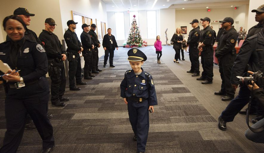 """Detroit Police """"Chief for a Day"""" Carter Widmer, 7, arrives at the Detroit Public Safety Headquarters on Wednesday, Dec. 23, 2015, in Detroit. Widmer donated $250 of his Christmas money to the Detroit Police K-9 Unit. (John T. Greilick/Detroit News via AP)  DETROIT FREE PRESS OUT; HUFFINGTON POST OUT; MANDATORY CREDIT"""