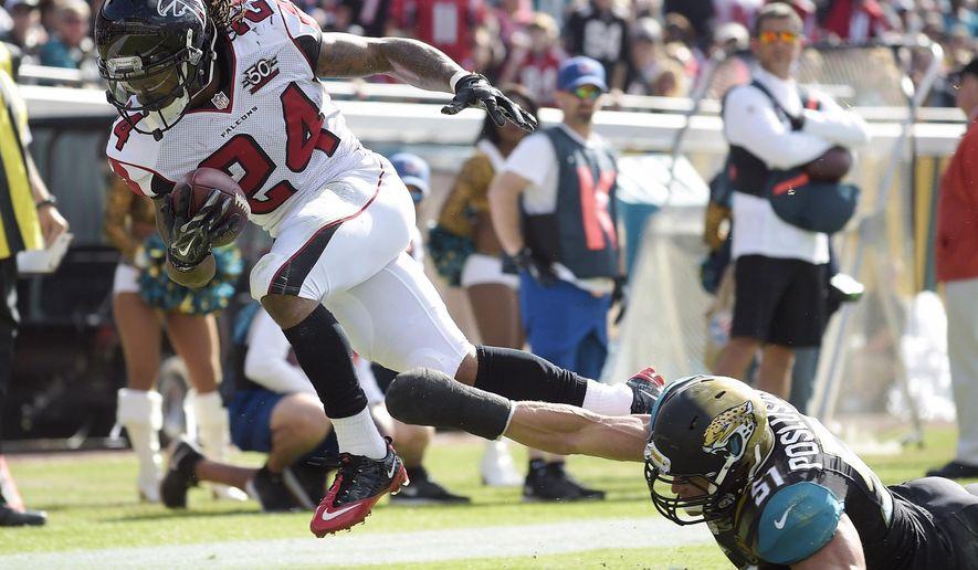 Atlanta Falcons running back Devonta Freeman (24) scores a touchdown on a 5-yard run past Jacksonville Jaguars middle linebacker Paul Posluszny, right, during the first half of an NFL football game in Jacksonville, Fla., Sunday, Dec. 20, 2015. (AP Photo/Phelan M. Ebenhack)