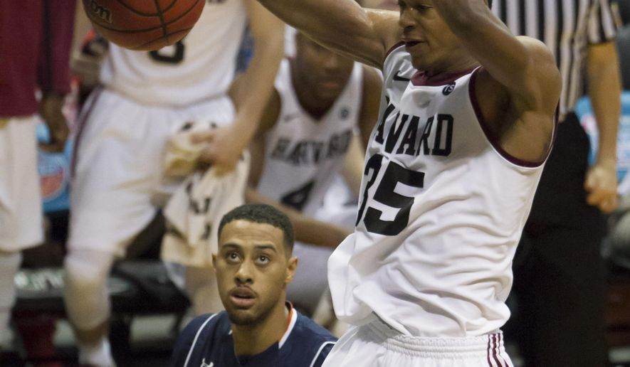 Harvard guard Agunwa Okolie (35) dunks as Auburn forward Devin Waddell (31) watches during the second half of an NCAA college basketball game at the Diamond Head Classic, Wednesday, Dec. 23, 2015, in Honolulu. Harvard won 69-51. (AP Photo/Eugene Tanner)