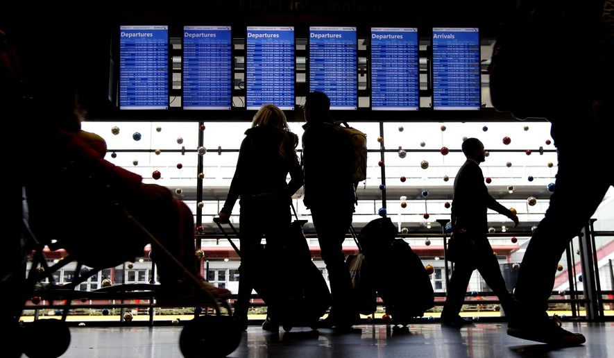 FILE - In this Nov. 29, 2015 file photo, travelers walk to their gates at O'Hare International Airport in Chicago.  Airlines are shifting the timing of thousands of flights, even adding dozens of redeyes, as they try to avoid delays while hauling millions of passengers from now through the Christmas weekend. Success or failure could all depend on the weather.(AP Photo/Nam Y. Huh, File)