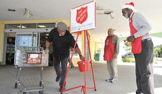 In this Dec. 9, 2015 photo, Walter Williams places his donation in a kettle next to Harold Pierce at a Publix store in Jacksonville, Fla. Pierce is among the top fundraisers for the regional Salvation Army Red Kettle Christmas campaign. At right is bell ringer Wilfred Jones. (Bruce Lipsky/The Florida Times-Union via AP)
