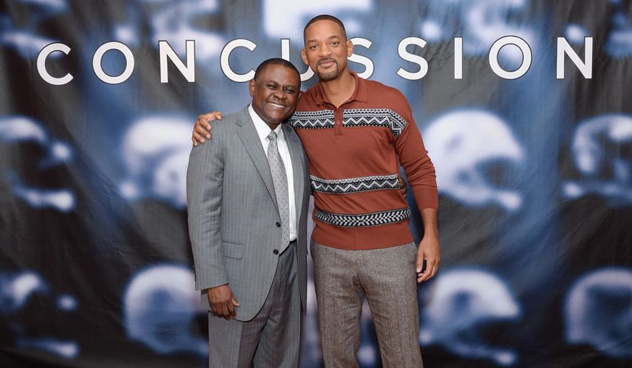 "In this Dec. 14, 2015, file photo, Dr. Bennet Omalu, left, and actor Will Smith pose together at the cast photo call for the film ""Concussion"" at The Crosby Street Hotel in New York. The movie releases in U.S. theaters on Dec. 25, 2015.  (Photo by Evan Agostini/Invision/AP, File)"