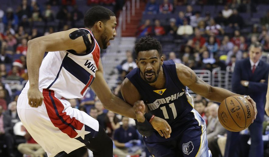 Memphis Grizzlies guard Mike Conley, right,  drives around Washington Wizards guard Garrett Temple, left, during the first half of an NBA basketball game, Wednesday, Dec. 23, 2015, in Washington. (AP Photo/Carolyn Kaster)