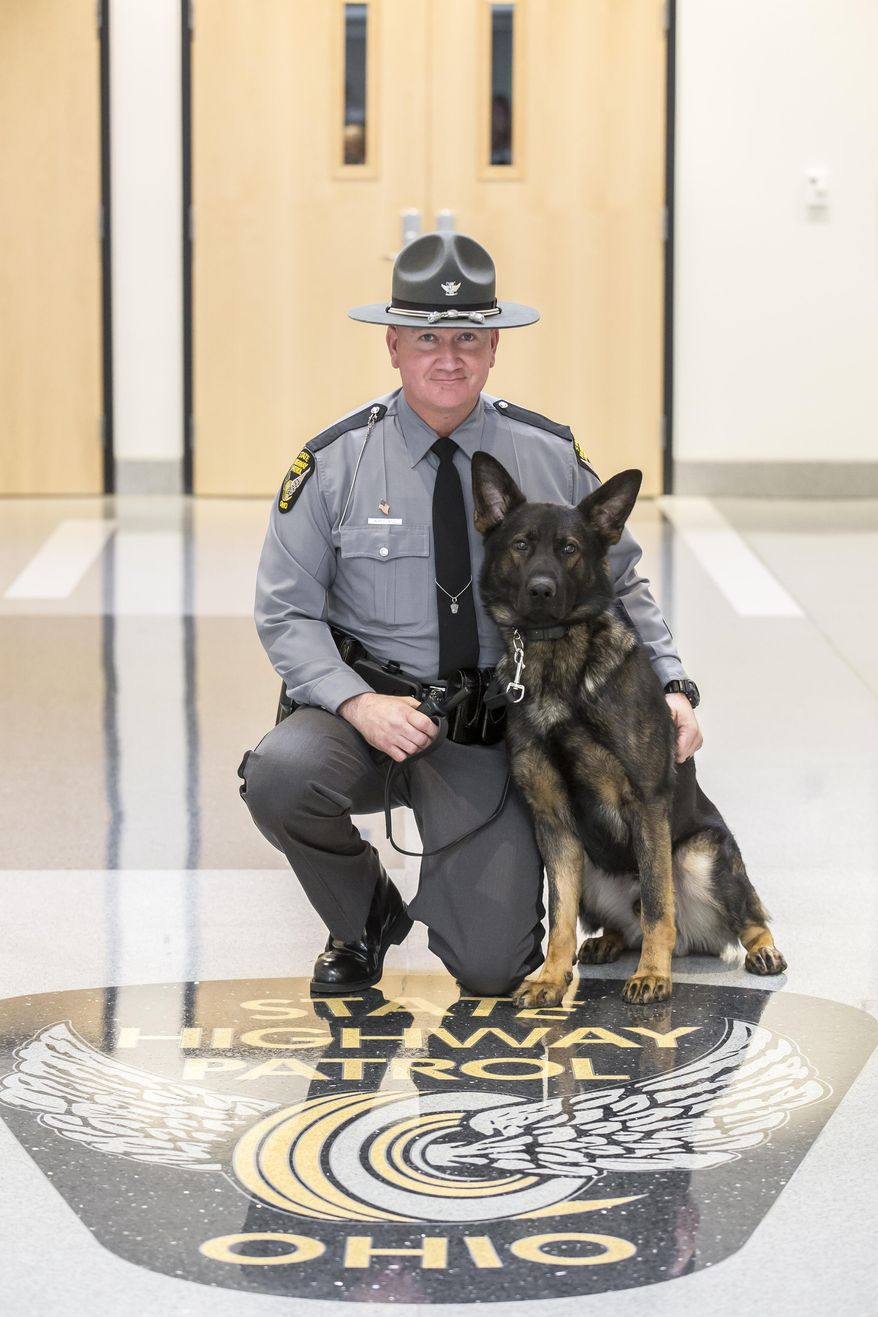 This photo provided by the Ohio State Highway Patrol shows the agency's new K-9, Fox, and its handler, Trooper Jeremy Wheeland of Piqua, at the patrol academy in Columbus, Ohio, Tuesday, Dec. 22, 2015. The State Highway Patrol in Ohio has switched to buying and training its own canines instead of using a contractor, and the program's first graduate is Fox, an 18-month-old male German Shepherd. (Ohio State Highway Patrol via AP)