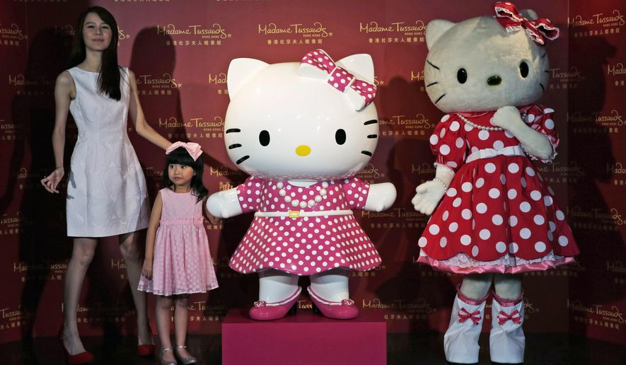 """FILE - In this July 24, 2014 file photo, a model dressing as Japanese character Hello Kitty, right, along with Hong Kong actresses Priscilla Wong, left, and Celine Yeung, second from left, pose with a new figure of Hello Kitty unveiled at the Madame Tussauds in Hong Kong, to mark the 40th anniversary of the birth of the popular Sanrio character. The Japanese company that owns the Hello Kitty brand said it has fixed a security leak in an online fan site for the famous character that compromised the personal information of 3.3 million users. Sanrio Co.'s digital arm said Tuesday, Dec. 22, 2015,  that it """"corrected"""" a security vulnerability on the SanrioTown.com website and was carrying out an investigation. The leak was discovered Saturday, Dec. 19, by a security researcher. (AP Photo/Kin Cheung, File)"""