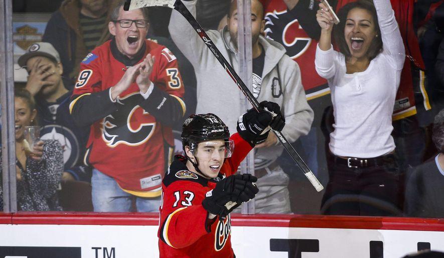 Calgary Flames' Johnny Gaudreau celebrates his third goal during third period of an NHL hockey game in Calgary, Alberta, Tuesday, Dec. 22, 2015. (Jeff McIntosh/The Canadian Press via AP) MANDATORY CREDIT