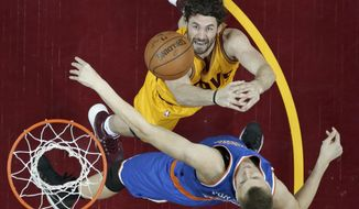 Cleveland Cavaliers' Kevin Love, top, and New York Knicks' Kristaps Porzingis, from Latvia, battle for a rebound in the first half of an NBA basketball game Wednesday, Dec. 23, 2015, in Cleveland. (AP Photo/Tony Dejak)